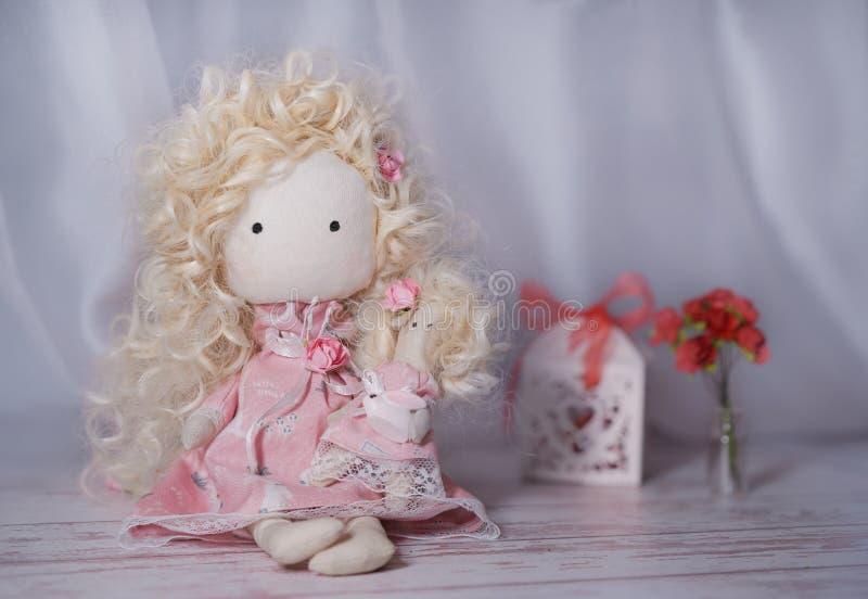 在一张白色木桌上的手工制造玩偶与纸花和礼物盒 免版税库存照片