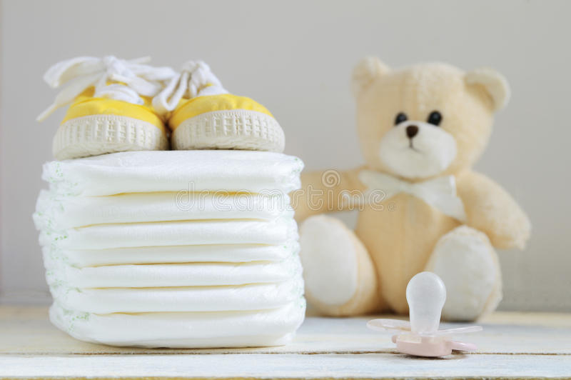 在一张白色木桌上的有些尿布 运动鞋、安慰者和玩具熊 免版税库存照片