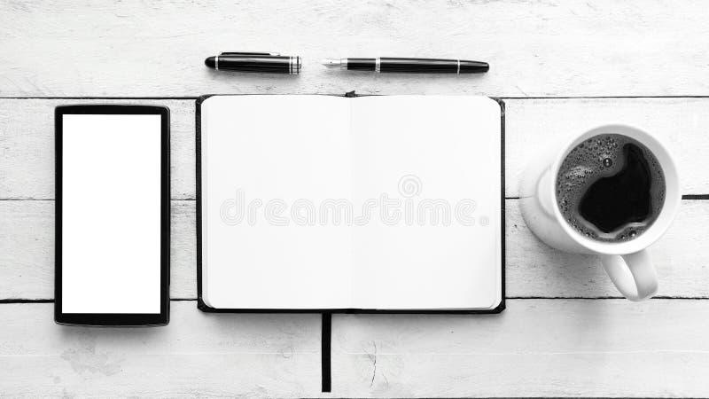 在一张白色木桌上的笔记本在机动性、一支笔和一些咖啡旁边在杯子 顶视图和空的拷贝空间 库存图片
