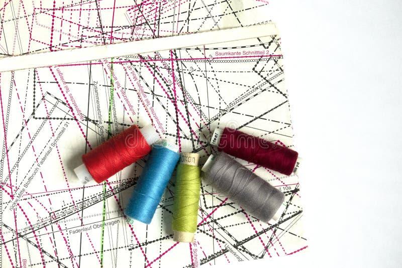 在一张白色木桌上的缝合的供应:缝合针线,剪刀,螺纹,布,针,厘米一个大短管轴  免版税库存图片