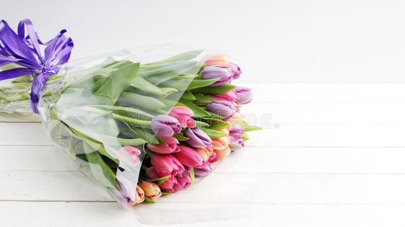 在一张白色木桌上的花束五颜六色的郁金香 免版税库存图片