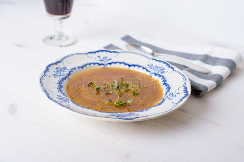在一张白色木桌上的经典法国葱汤与一些红色wi 免版税库存图片