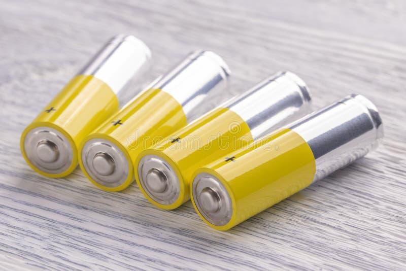 在一张白色木桌上的AA电池 库存照片