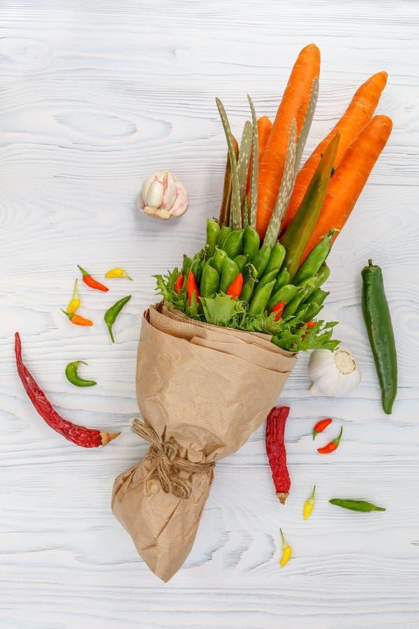 在一张白色木桌上说谎包括红萝卜、豌豆荚、沙拉、胡椒和芦荟的素食花束 附近大蒜,红色d 图库摄影