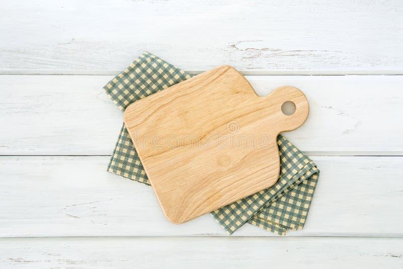 在一张白色木桌安置的餐巾的木切板, t 库存图片