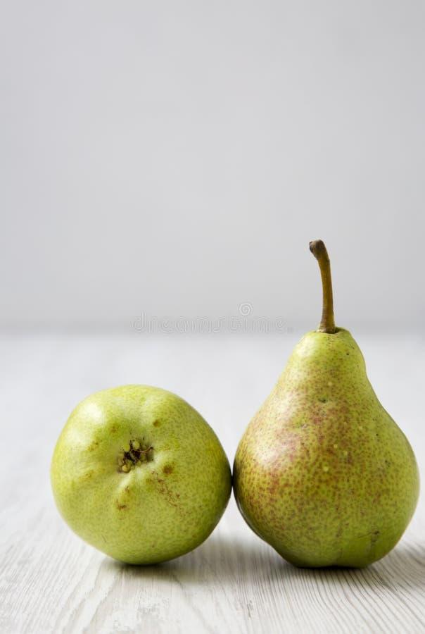 在一张白色木桌,侧视图上的两个梨 库存照片