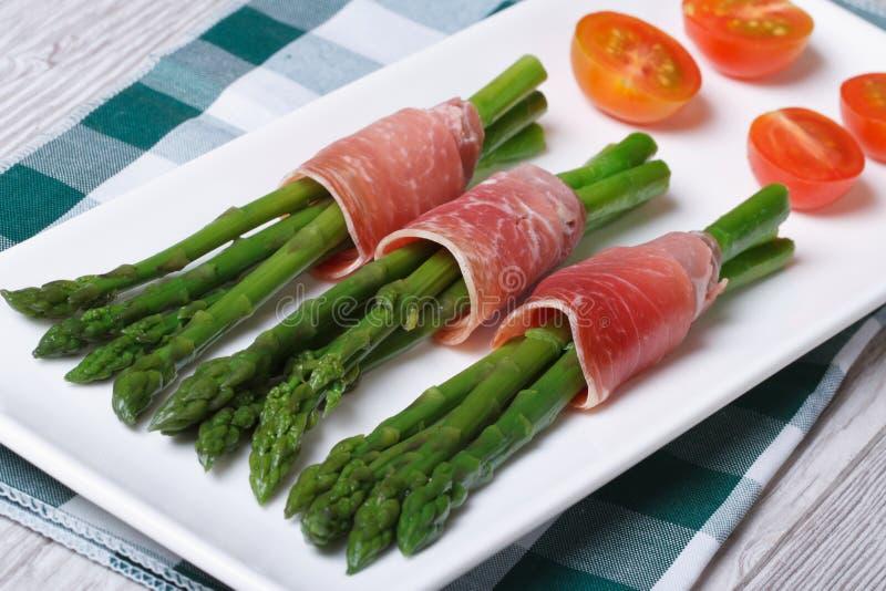 在一张白色板材顶视图的火腿包裹的绿色芦笋 库存照片