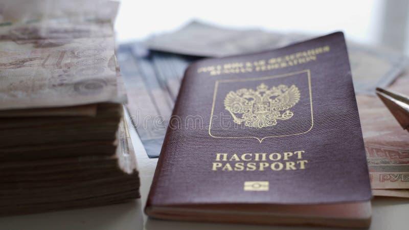 在一张白色桌上有很多金钱、护照和一架小飞机由金钱制成 休息的概念 库存图片