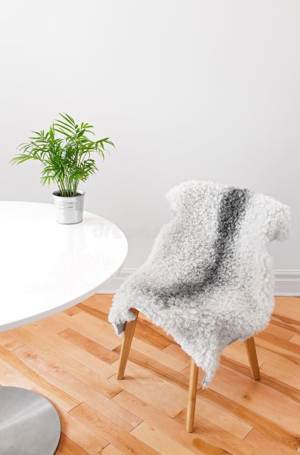 在一张白色桌上的用羊皮盖的椅子和植物 图库摄影