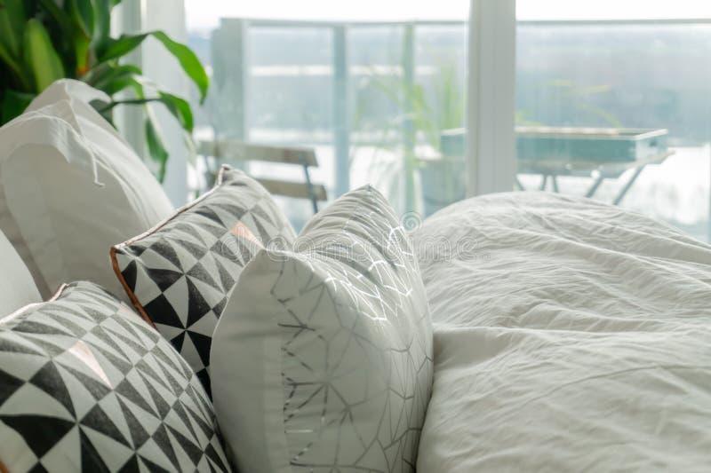 在一张真正的床上的蓬松,装饰枕头,与起皱纹的板料和灰色,黑白强调色 阳台视图在显示 图库摄影