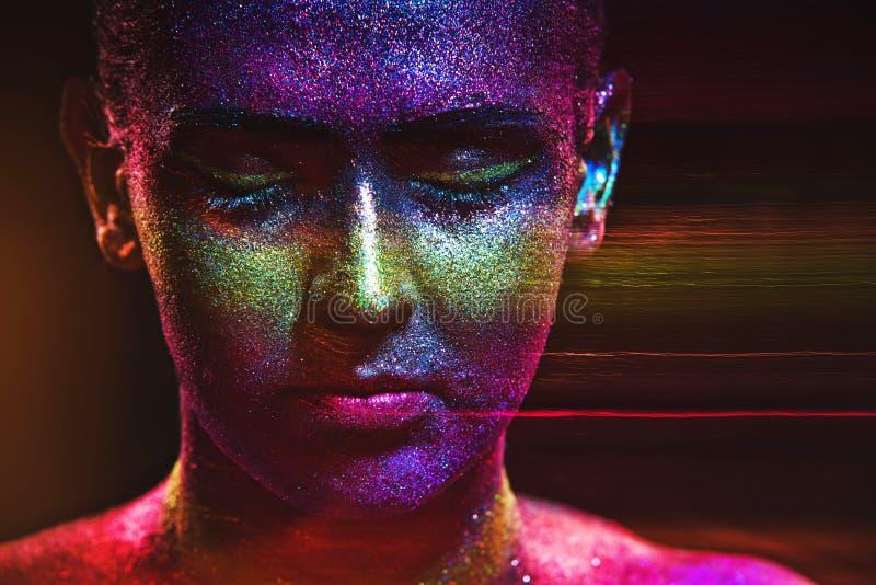 在一张美丽的妇女面孔的闪烁构成在黑背景 图库摄影