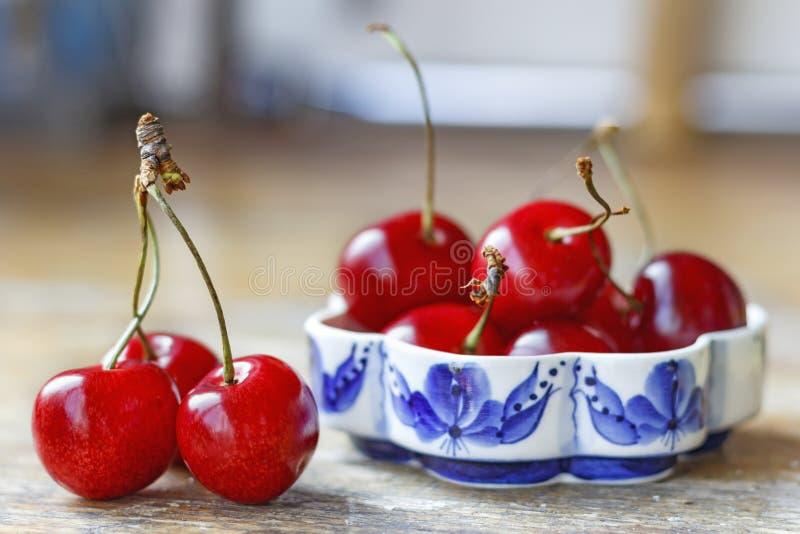 在一张老木桌上的甜红色樱桃 免版税库存照片