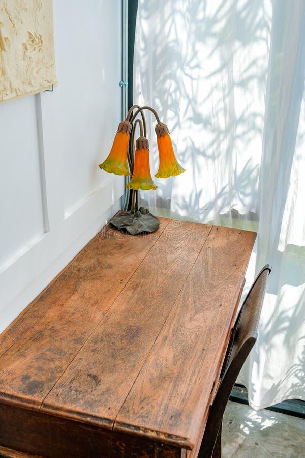 在一张老葡萄酒木书桌的葡萄酒灯有白色墙纸的 免版税库存照片