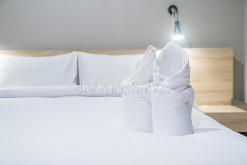 在一张舒适的床上的白色毛巾与舒适卧室 免版税库存照片