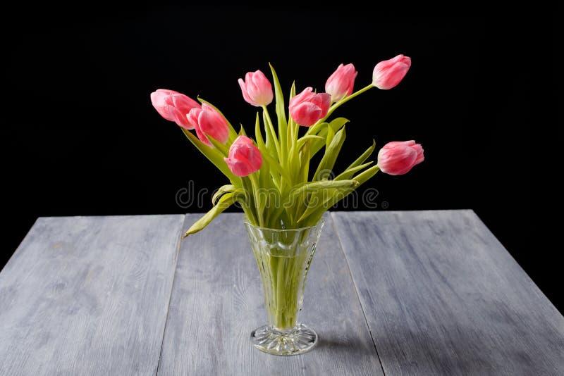 在一张蓝灰色木头桌上的郁金香 免版税库存图片