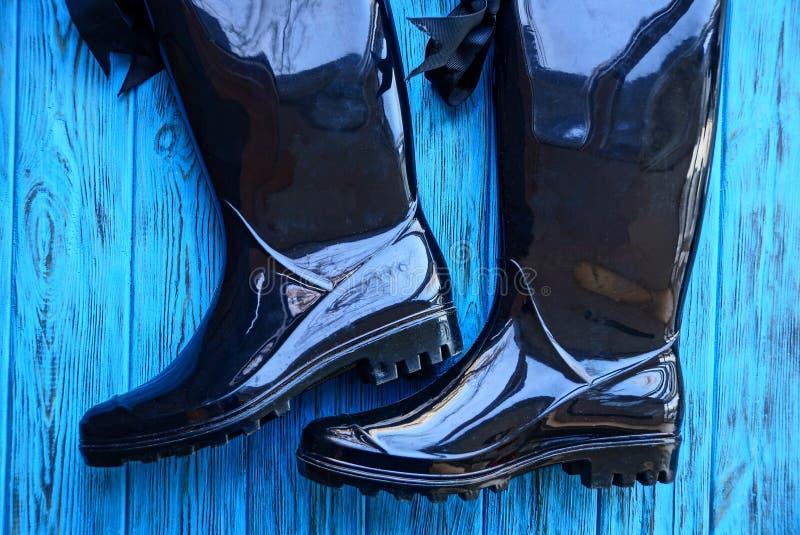在一张蓝色木桌上的黑胶靴 库存照片