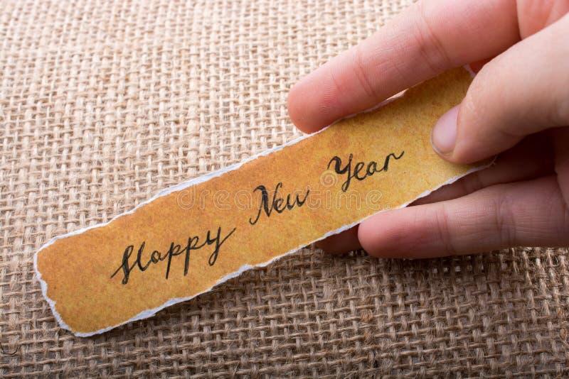 在一张被撕毁的纸在手中写的新年好 免版税图库摄影