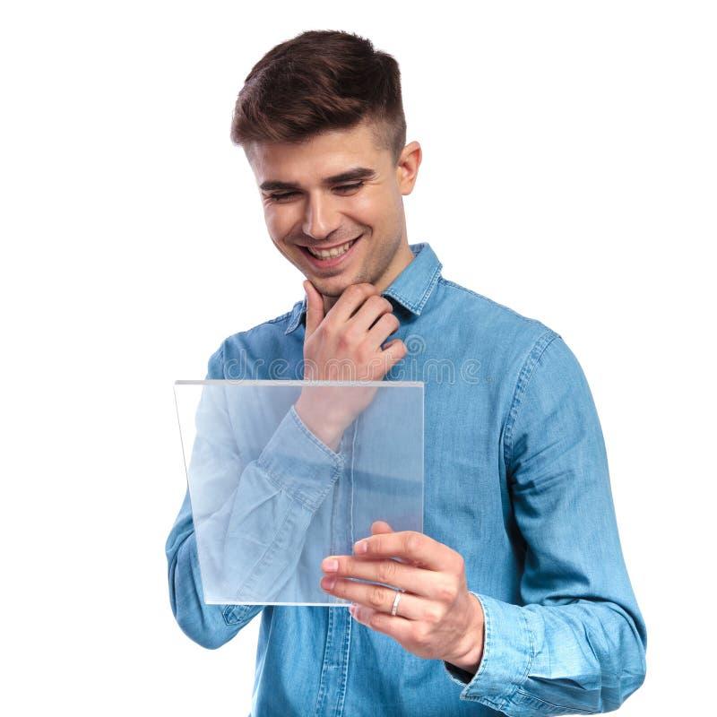在一张透明未来派ebook桌上的年轻偶然人读书 库存照片