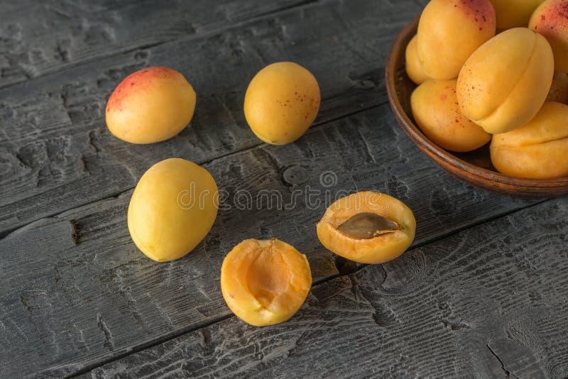 在一张黑木桌上驱散的杏子 库存图片