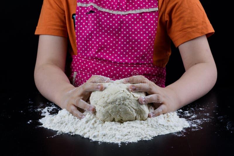 在一张黑桌上的揉的面团在面包店 Baker& x27; s递prepa 库存图片