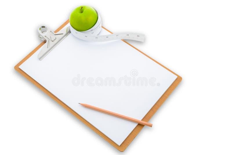 在一张绿色苹果和剪贴板附近被包裹的测量的磁带 免版税库存图片