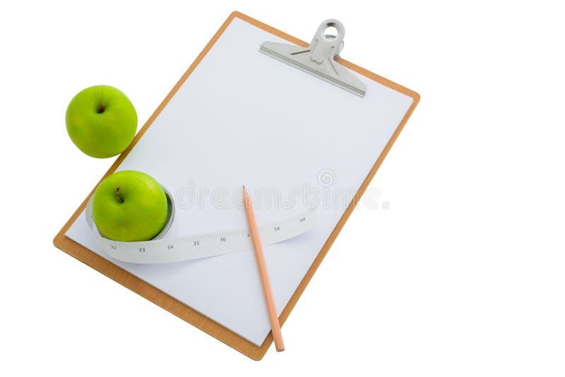 在一张绿色苹果和剪贴板附近被包裹的测量的磁带 库存图片