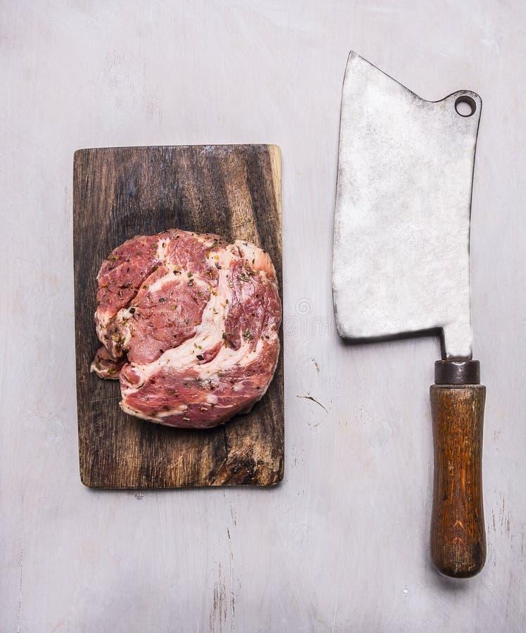 在一把切板和葡萄酒切肉刀的未加工的猪肉牛排在木土气背景顶视图关闭 免版税图库摄影
