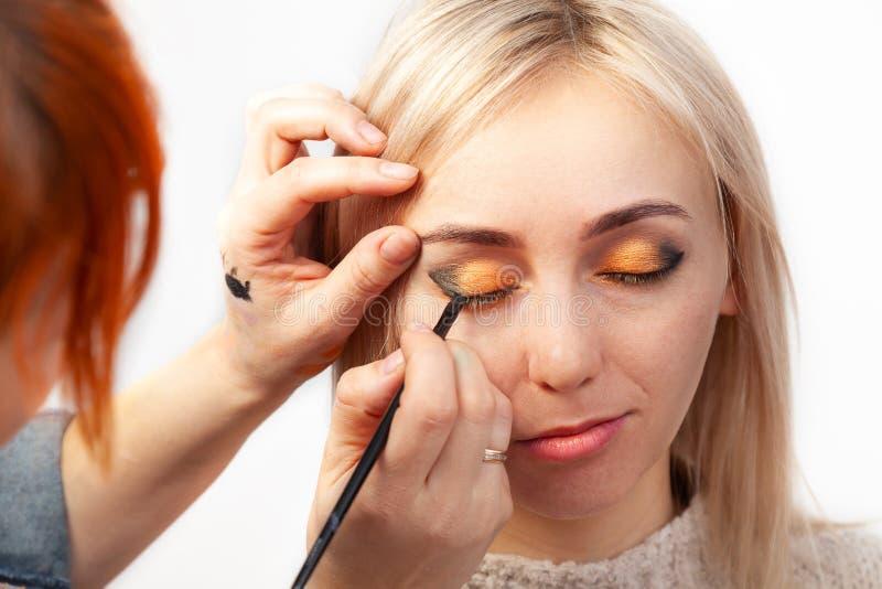 在一把刷子帮助下的化妆师在一只手上画在模型的眼睛的一个箭头,用另一只手向后拉 免版税库存照片