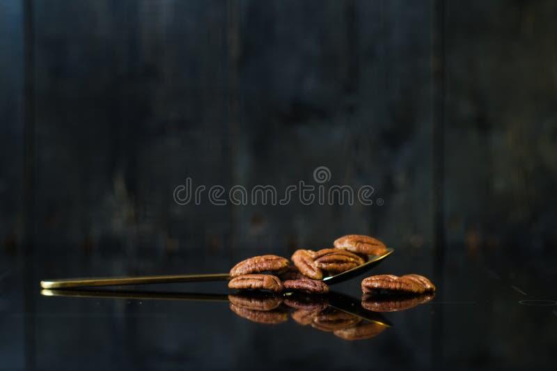 在一把匙子的胡桃在镜子,黑背景,侧视图 免版税库存图片