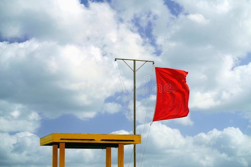 在一把救生员椅子旁边的红旗在海滩 游泳在海不允许 免版税图库摄影