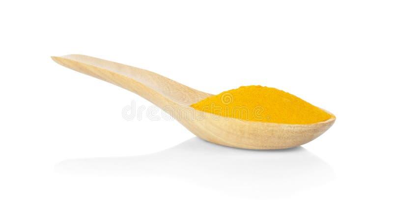 在一把木匙子的姜黄粉末在白色背景 免版税图库摄影