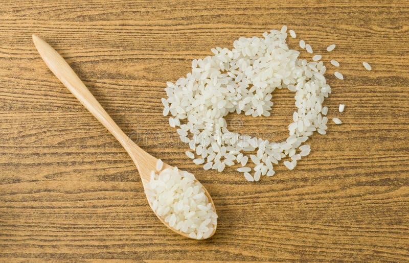 在一把木匙子的未煮过的日本米 免版税图库摄影