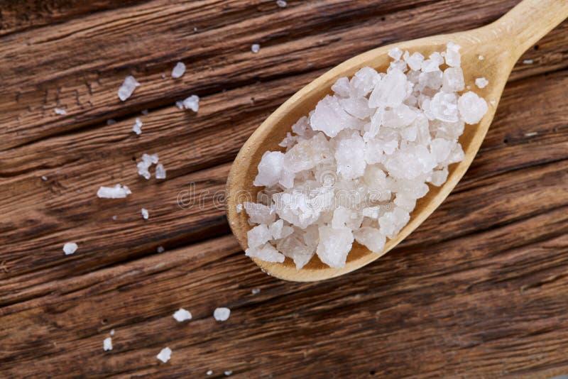在一把木匙子的水晶海盐在黑暗的葡萄酒木背景,顶视图,特写镜头,选择聚焦 免版税图库摄影