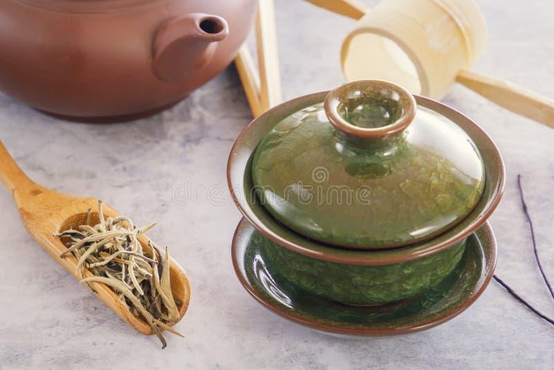 在一把木匙子的茶道的绿茶,属性和繁体中文瓷绿化杯子 免版税库存图片