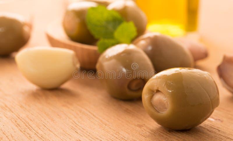 在一把木匙子的绿橄榄装饰与蓬蒿、大蒜在玻璃碗附近和橄榄油刺激 免版税库存照片