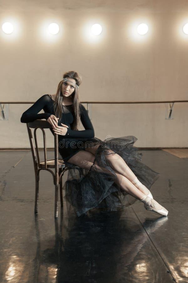 在一把木椅子的当代跳芭蕾舞者在重复 免版税图库摄影