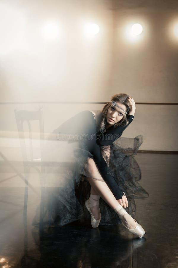 在一把木椅子的当代跳芭蕾舞者在重复 免版税库存照片
