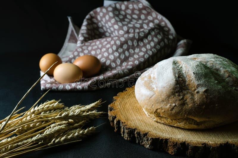 在一把木锯的家制面包有麦子的耳朵的在黑暗的背景的 库存图片