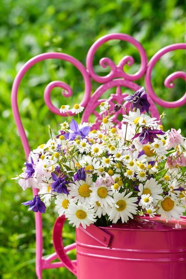 在一把桃红色喷壶的五颜六色的野花花束 库存图片