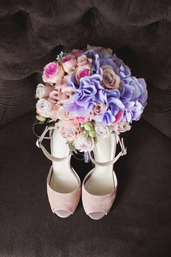 在一把棕色扶手椅子的裸体米黄婚礼鞋子 花束新娘新娘新郎现有量 库存照片