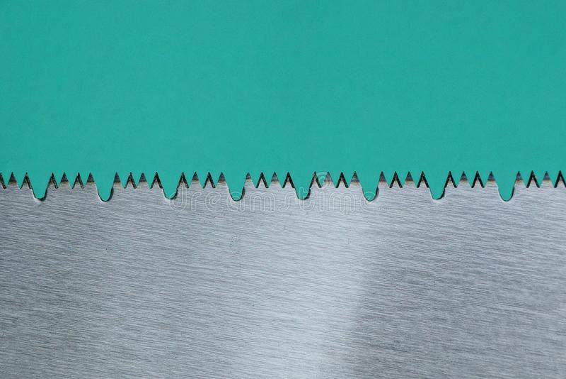 在一把灰色引形钢锯的钢牙在绿色背景 免版税库存图片