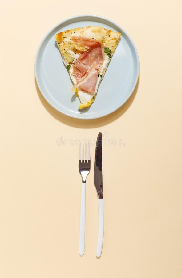 在一把蓝色板材叉子的在黄色背景的比萨和刀子 顶视图 免版税库存照片