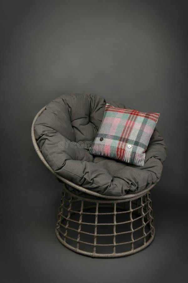 在一把藤椅的看法的边和在灰色的软的就座和五颜六色的坐垫 库存照片