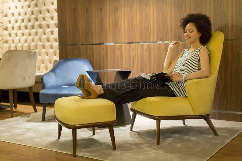 在一把黄色椅子和读书的年轻女人sittinh 免版税库存照片