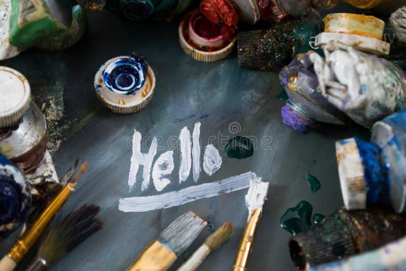 在一支管的明亮的油漆在一个肮脏的调色板 油漆在使用中 绘的你好 图库摄影