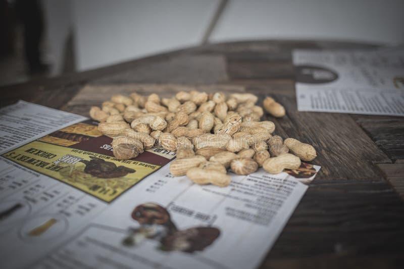 在一木桌食物和破裂的snaks的花生坚果 免版税图库摄影