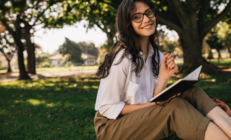 在一本书的妇女文字在公园 免版税库存图片