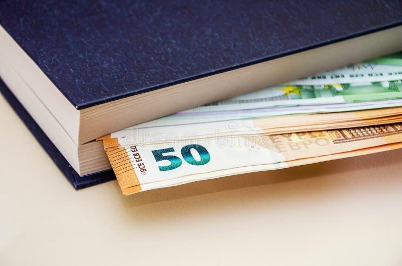 在一本书的50和100欧元在桌,特写镜头上 免版税库存照片