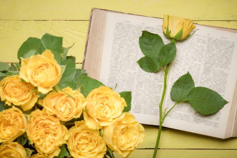 在一本开放旧书的黄色玫瑰 免版税库存照片