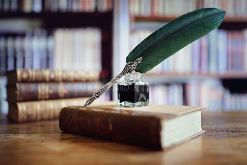 在一本旧书的翎毛钢笔在图书馆里 免版税库存图片